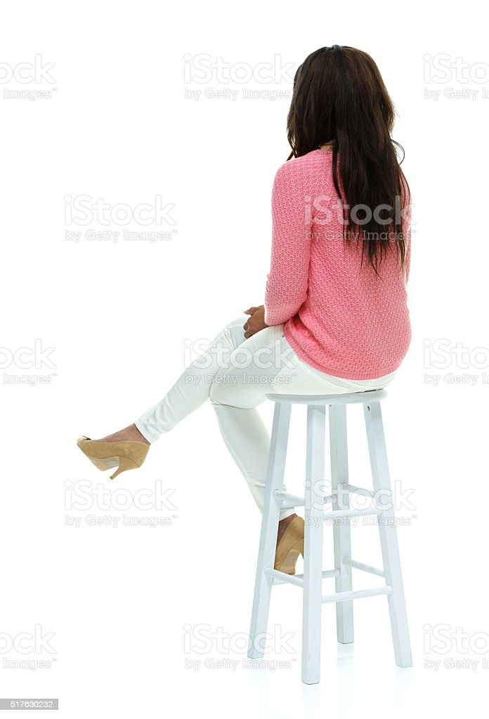 Rear View Of Fashionable Woman Sitting On Stool Stock