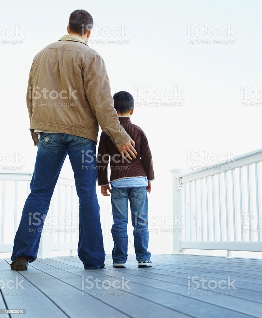 Rear view of father and son standing together at porch royalty-free stock photo