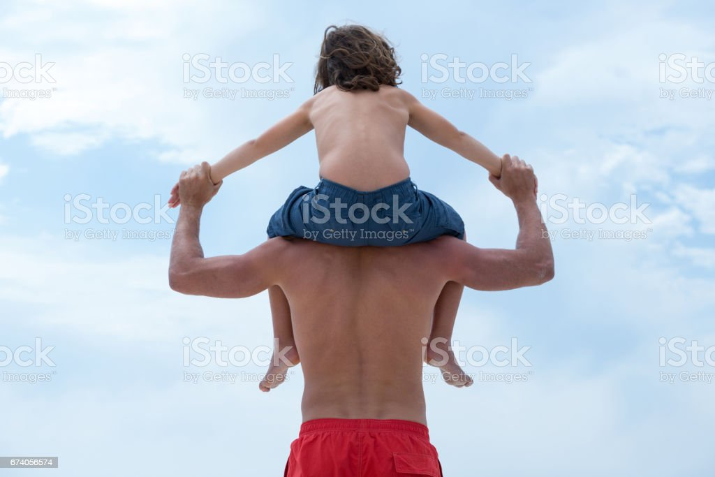 Rear view of father carrying son and holding hands royalty-free stock photo