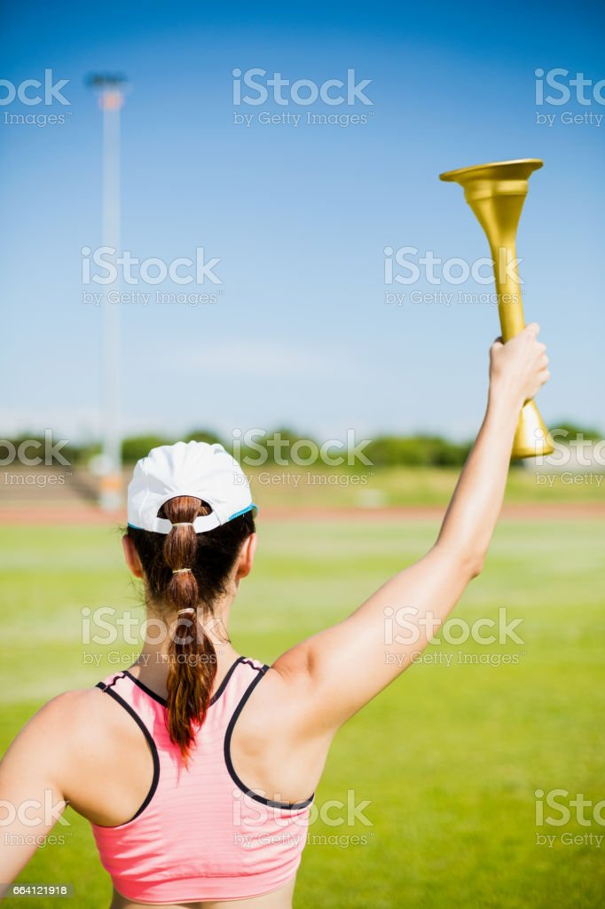 Rear view of female athlete holding a fire torch foto stock royalty-free