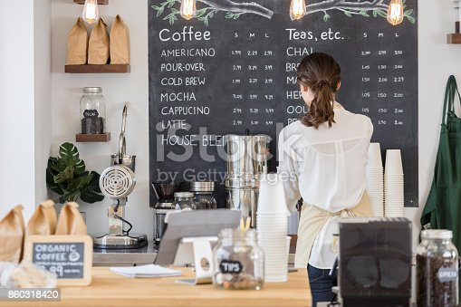 istock Rear view of female barista working in cafe 860318420