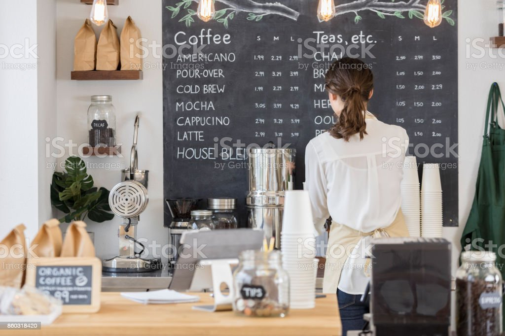 Rear view of female barista working in cafe stock photo