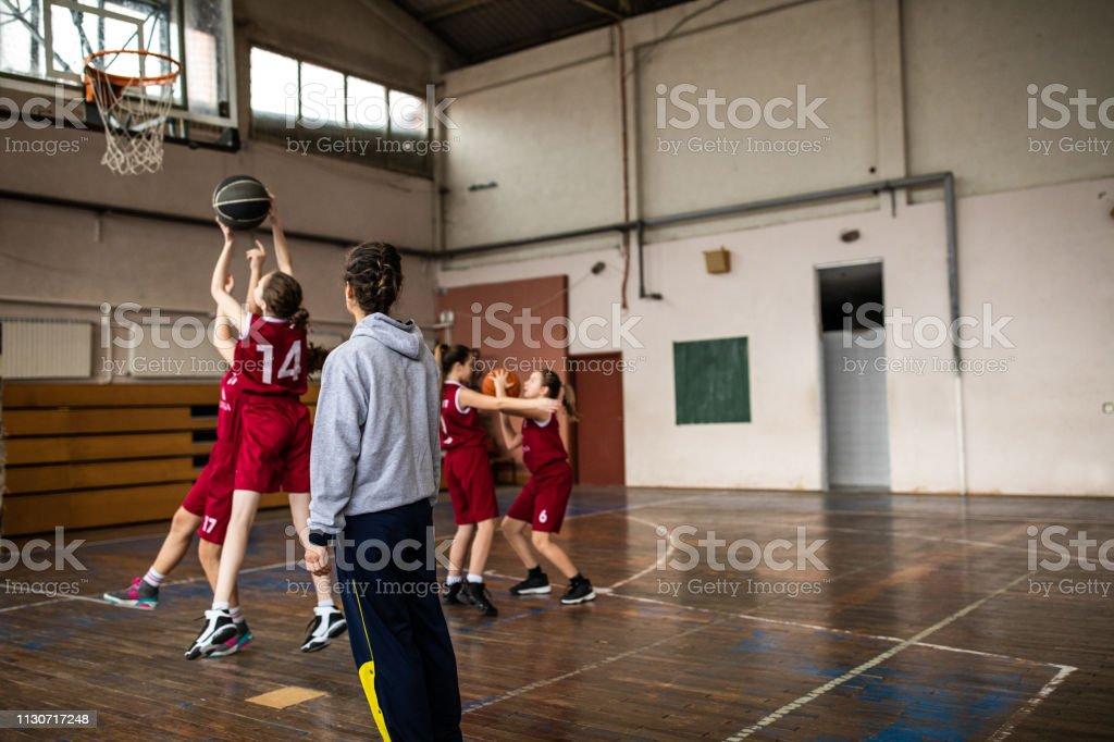 Teenage girls playing basketball at school gym, female coach...
