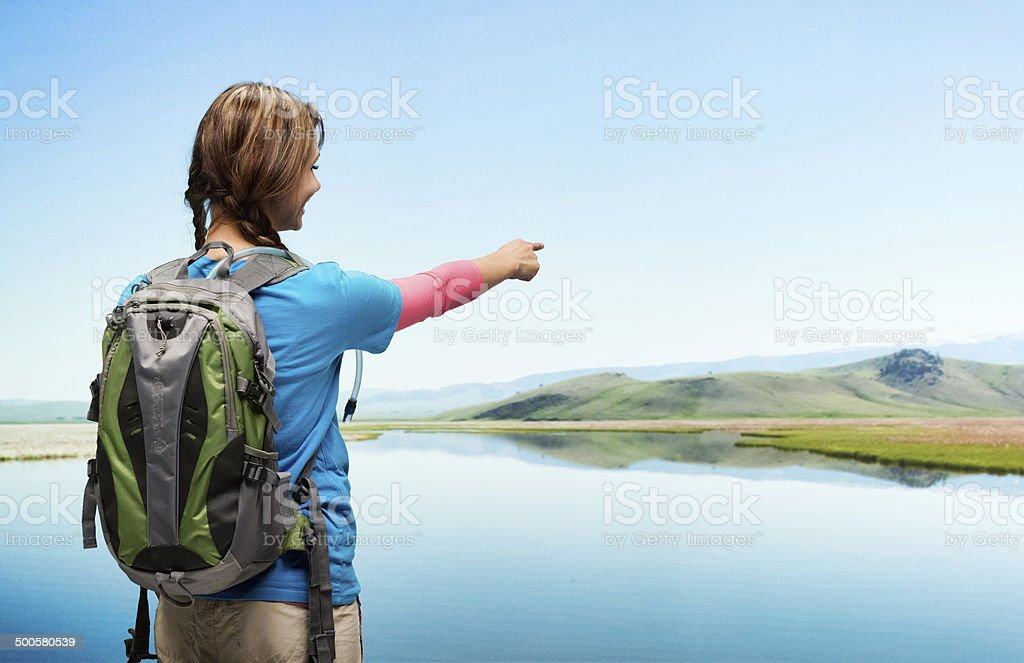 Rear view of female hiker pointing stock photo