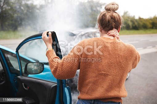 istock Rear View Of Female Motorist With Head Injury Getting Out Of Car After Crash 1156650366