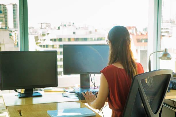 Rückansicht der Büroangestellten, die tippt, während ihr Computer durch Stromausfall leer ausgeht – Foto