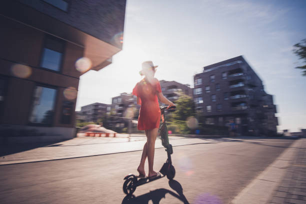 rear view of female on electric scooter. - electric push scooter stock photos and pictures