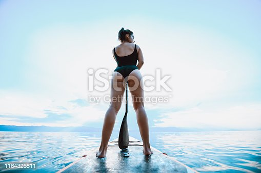Rear View Of Female Paddle Boarding