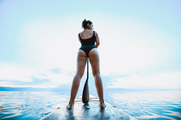 Rear View Of Female Paddle Boarding stock photo