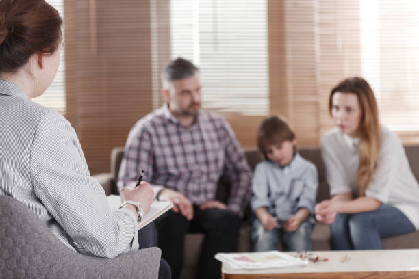 Rear view of female psychologist helping young family with a kid to solve child development problems. Family sitting on a sofa in the blurred background stock photo