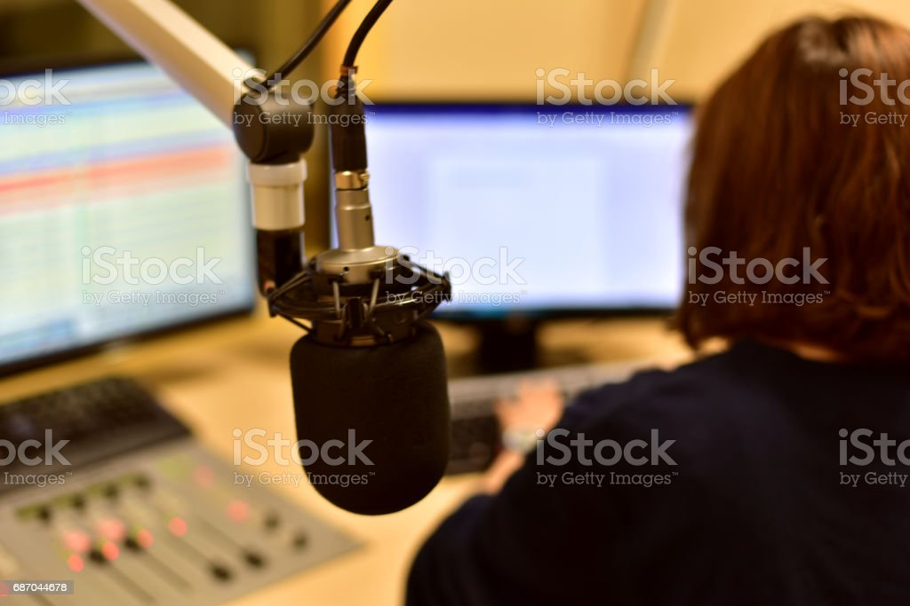 Rear view of female radio host working in front of a microphone on the radio station stock photo