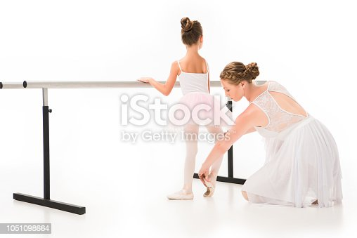 466300721 istock photo rear view of female teacher in tutu checking pointe shoes of little ballerina exercising at ballet barre stand isolated on white background 1051098664