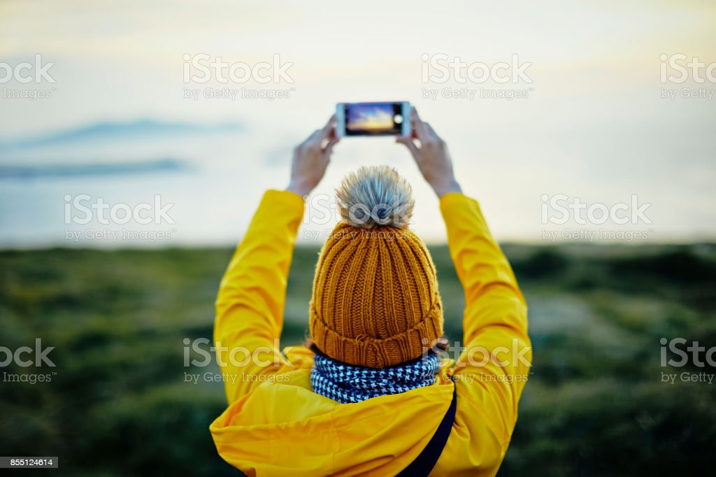 Rear view of female tourist photographing with smart phone on mountain by sea stock photo