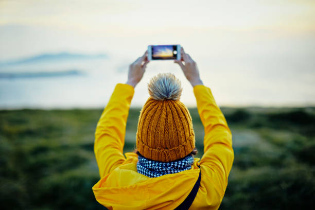 rear view of female tourist photographing with smart phone on mountain by sea - photo messaging stock photos and pictures