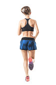 istock Rear view of fit athletic female sprinter running movement. 854374168