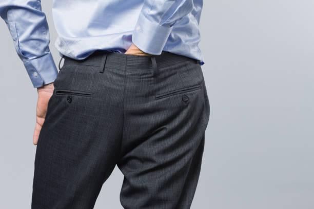 vue arrière de l'homme formellement habillé grattant ses fesses - homme slip photos et images de collection