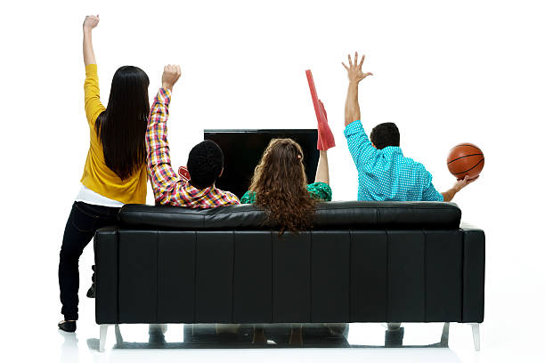 Rear view of four people watching tv and cheering stock photo