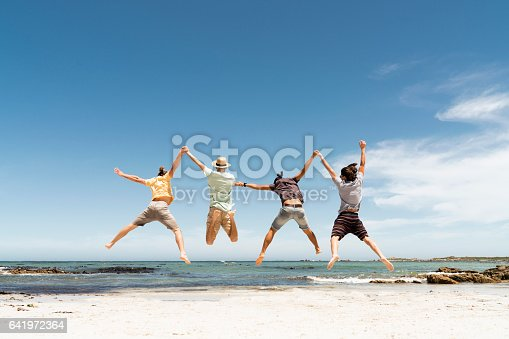 istock Rear view of friends jumping at beach 641972364