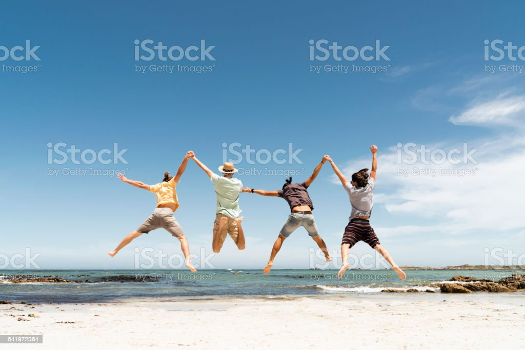 Rear view of friends jumping at beach stock photo