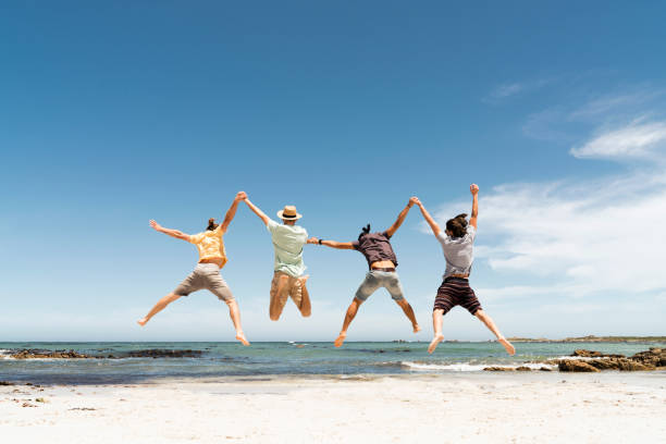 rear view of friends jumping at beach - four people stock photos and pictures