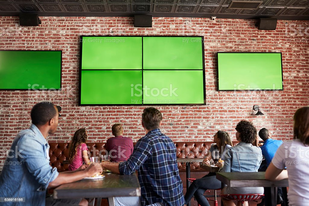 Rear View Of Friends Watching Game In Sports Bar On - foto de stock