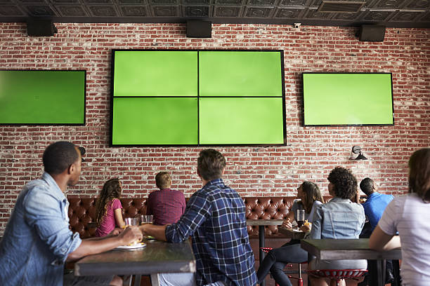 rear view of friends watching game in sports bar on - bar foto e immagini stock