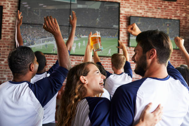 Rear View Of Friends Watching Game In Sports Bar On Screens stock photo
