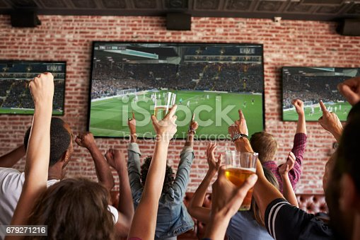 istock Rear View Of Friends Watching Game In Sports Bar On Screens 679271216