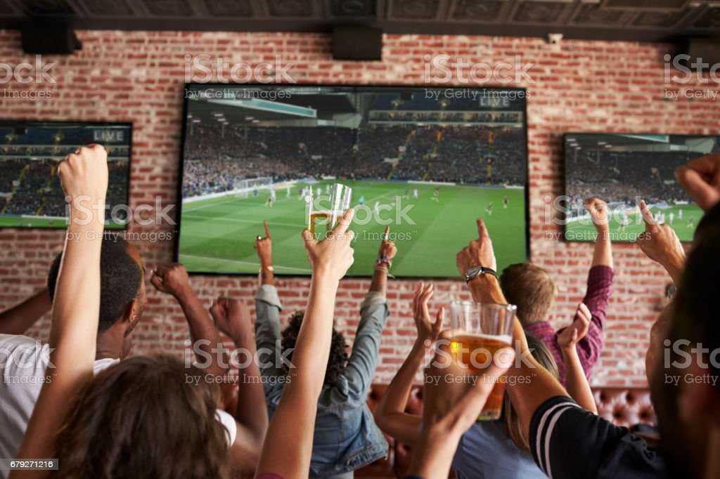 Rear View Of Friends Watching Game In Sports Bar On Screens - foto stock