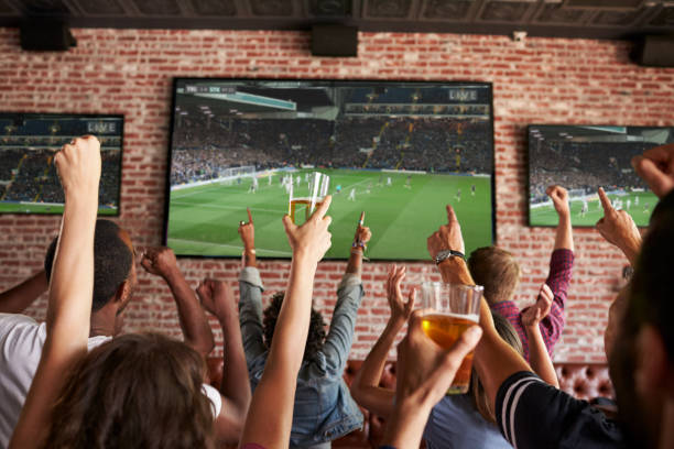 Rear View Of Friends Watching Game In Sports Bar On Screens – Foto