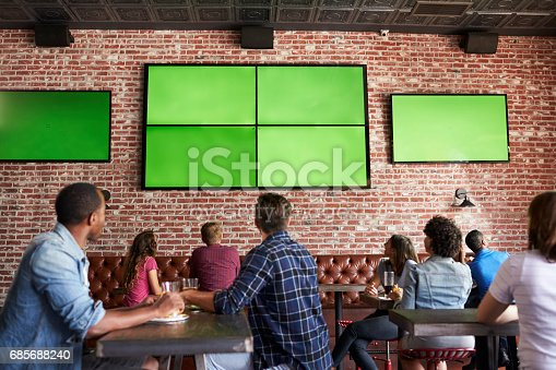 istock Rear View Of Friends Watching Game In Sports Bar On Screens 685688240