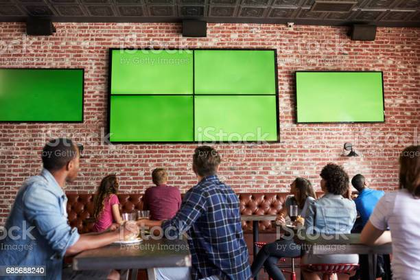 Rear view of friends watching game in sports bar on screens picture id685688240?b=1&k=6&m=685688240&s=612x612&h=mlsscpep4mlg y4xnegpfotusqvkxnyrrl5htvqvdas=
