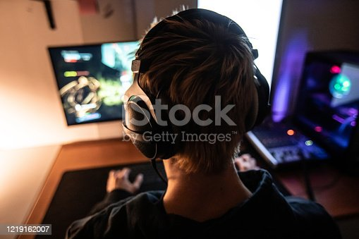Rear View of Gamer with Headset on Playing Online Video Games in Dark Room