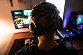 istock Rear View of Gamer with Headset on Playing Online Video Games in Dark Room - stock photo 1219162007