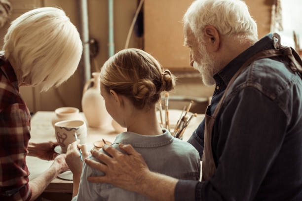 rückansicht des mädchen malerei tontopf und großeltern helfen beim workshop - handbemalte teller stock-fotos und bilder