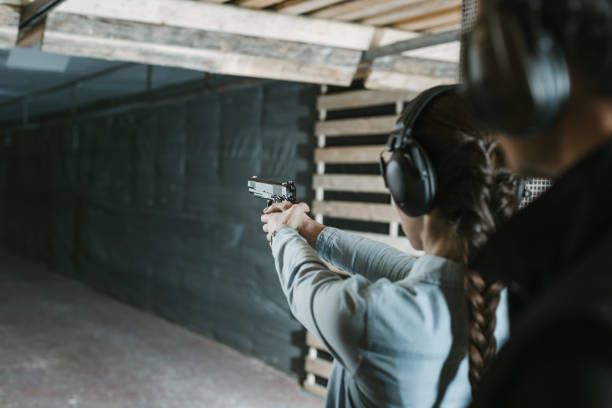 rear view of girl shooting with gun in shooting gallery rear view of girl shooting with gun in shooting gallery pistol stock pictures, royalty-free photos & images