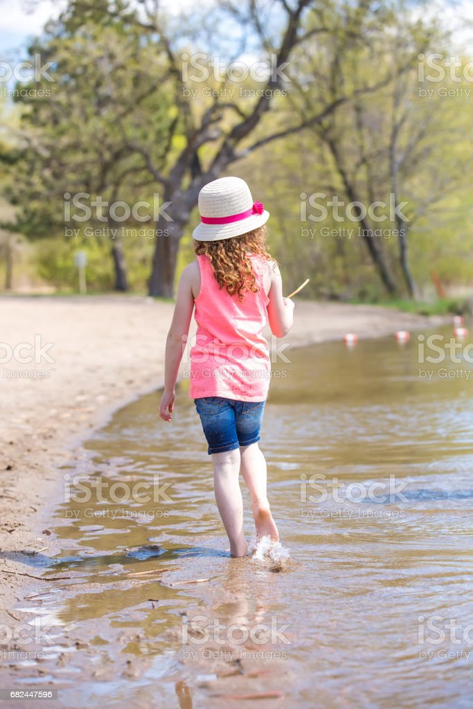 Rear View of Girl Walking Along Shoreline on Beach Lizenzfreies stock-foto