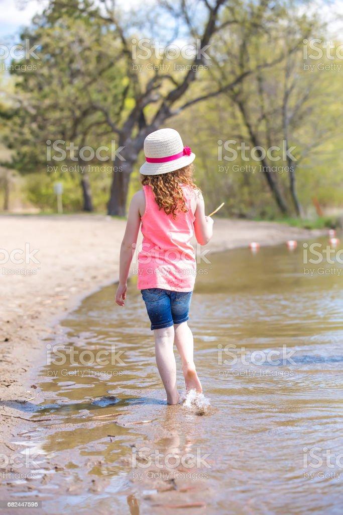 Rear View of Girl Walking Along Shoreline on Beach royalty-free stock photo