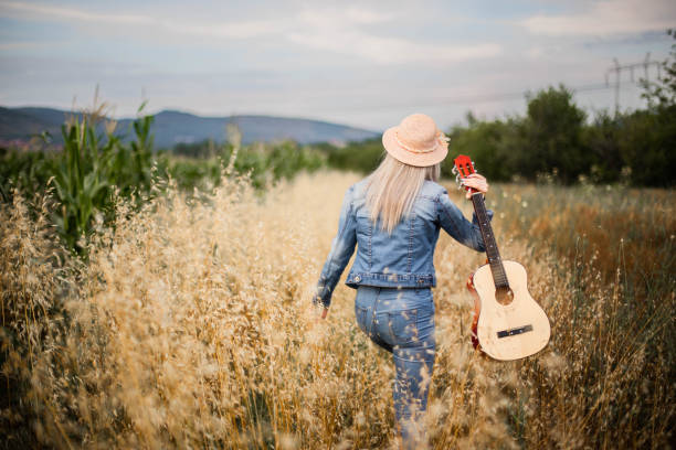 Rear view of girl with guitar at field