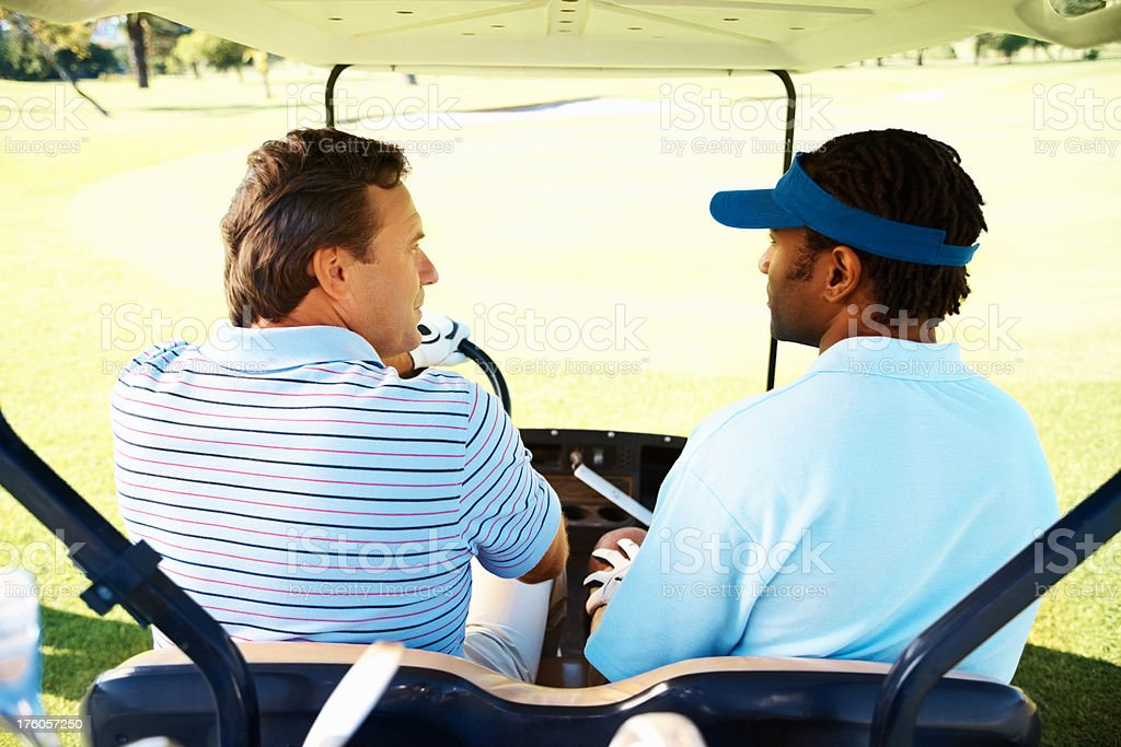 Rear view of golfers on a cart having royalty-free stock photo