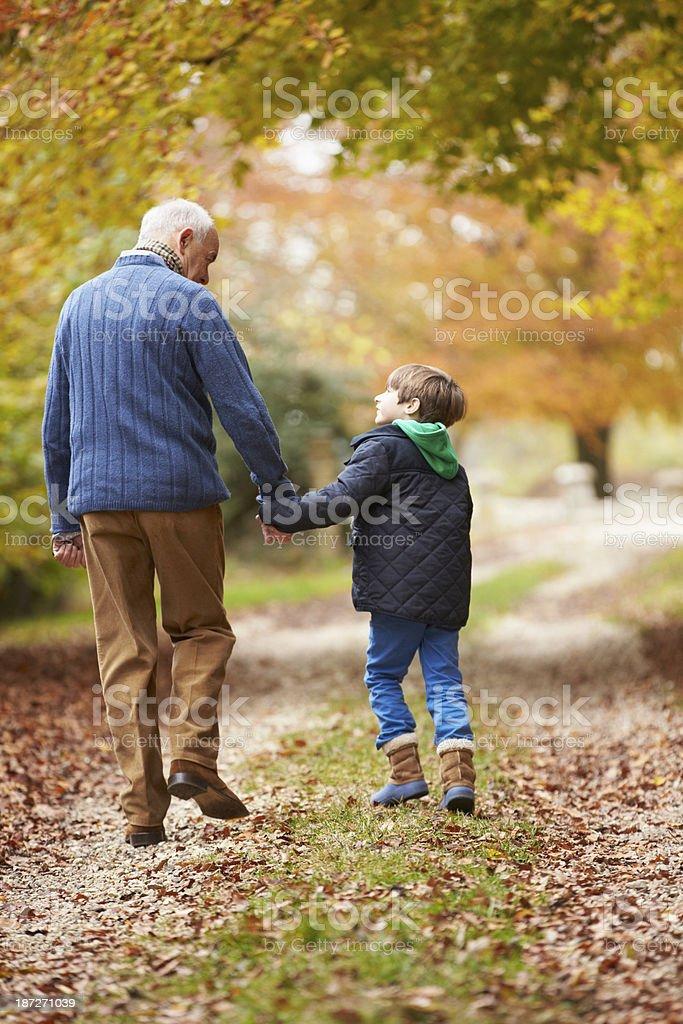 Vista posterior del abuelo y nieto caminando por la ruta - foto de stock