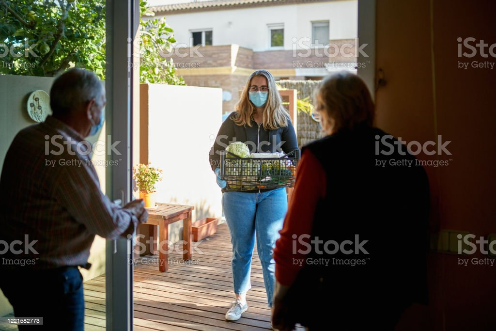 Rear view of Grandparents standing indoors while granddaughter delivers groceries outdoors during pandemic Rear view of Grandparents standing indoors while granddaughter delivers groceries outdoors during pandemic, Granddaughter is wearing mask and gloves. 16-17 Years Stock Photo