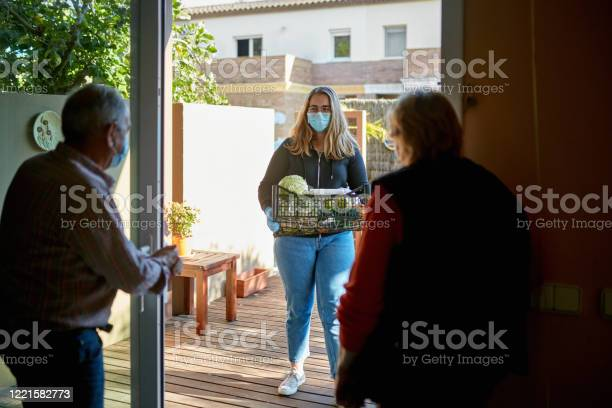 Rear View Of Grandparents Standing Indoors While Granddaughter Delivers Groceries Outdoors During Pandemic Stock Photo - Download Image Now