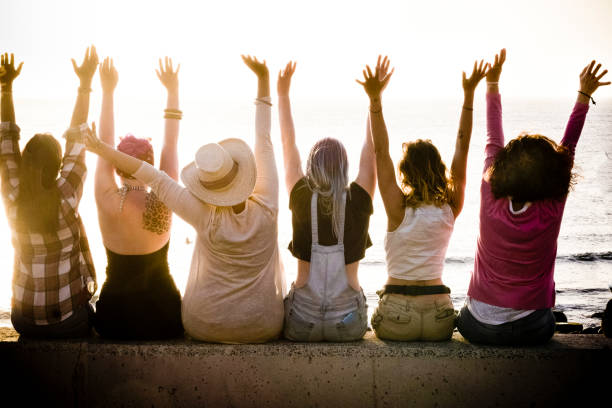 rear view of group of females caucasian friends enjoying at the sunset with ocean in background - success and satisfaction concept for nice people together with joy - friendship and vacation stock photo