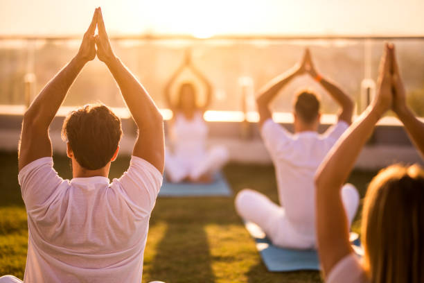 Rear view of group of people doing Yoga meditation exercises on a terrace. Back view of group of relaxed people exercising Yoga with their arms raised on a terrace. yoga class stock pictures, royalty-free photos & images