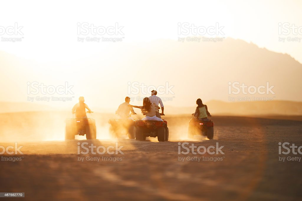 Rear view of group of people driving quad bikes. stock photo