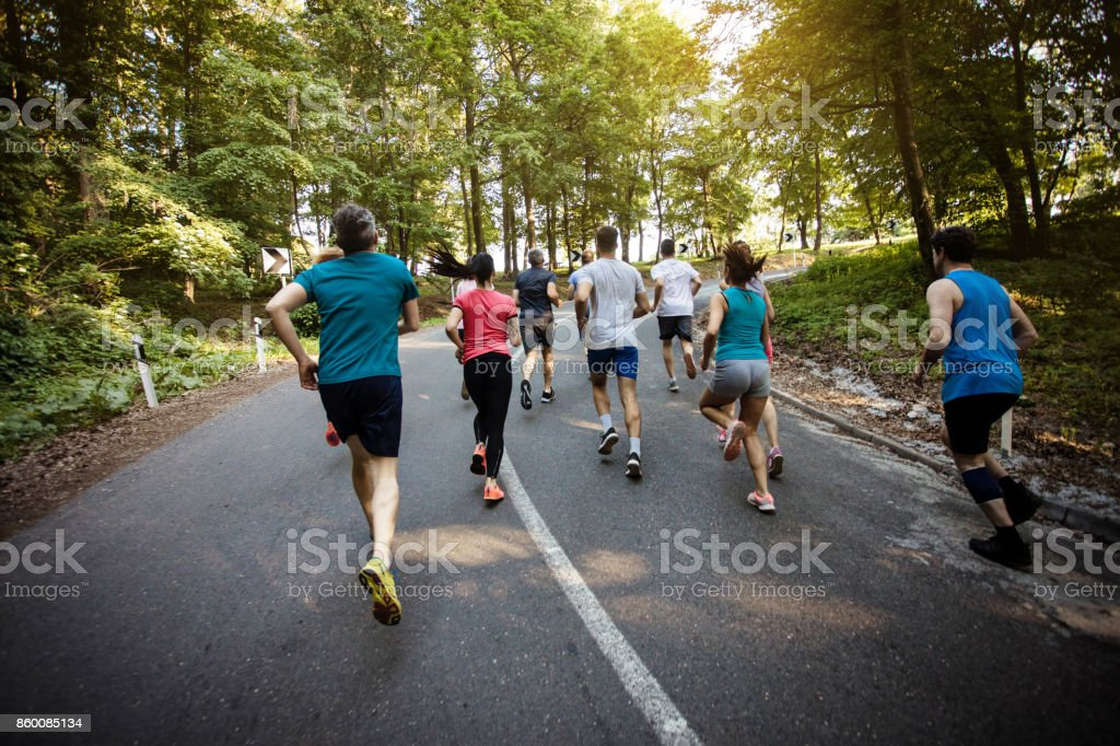 Rear view of group of runners taking part in marathon race. stock photo