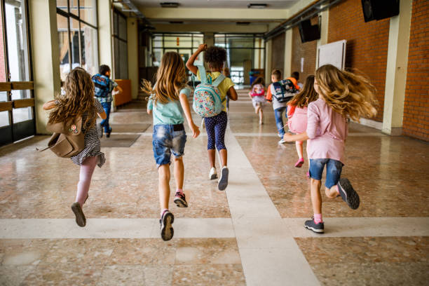 Rear view of group of school children running down the hallway. stock photo
