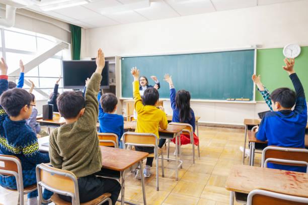 手を挙げながら学童群の背面図 - 小学校 ストックフォトと画像