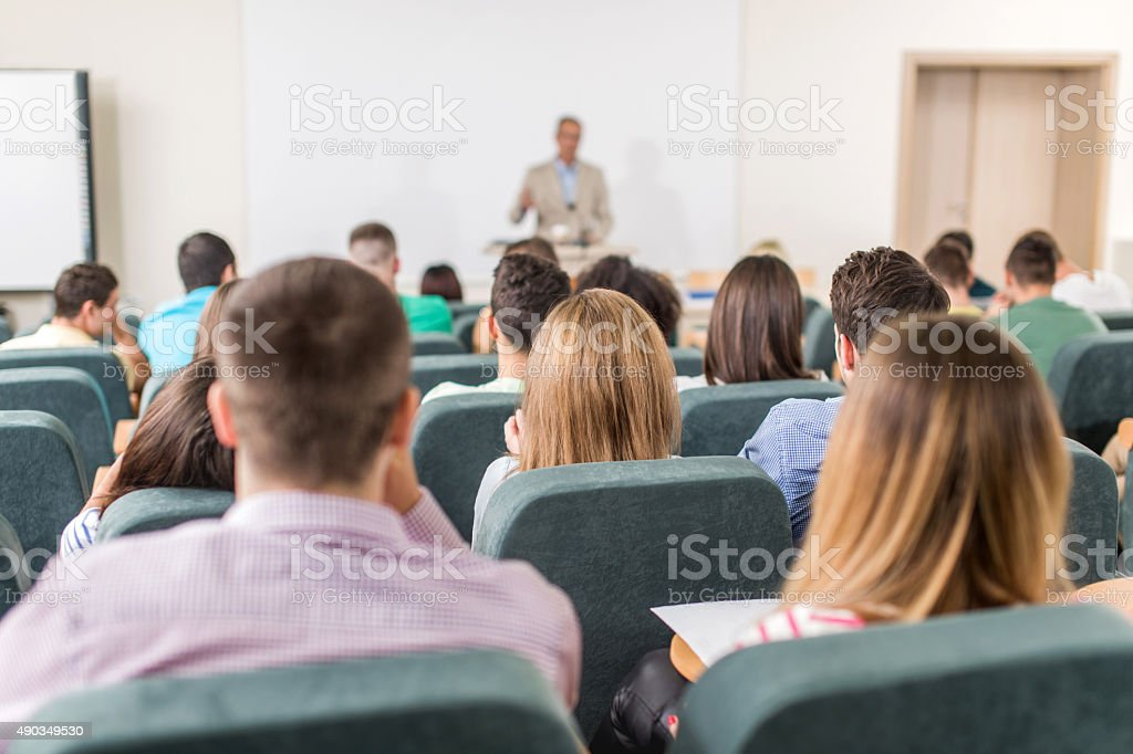 Rear view of group of students in amphitheatre during lecture. stock photo